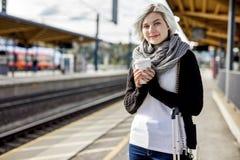 Femme tenant la tasse de café jetable à la station de train Photo libre de droits