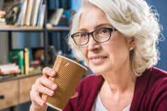 Femme tenant la tasse de papier Images stock