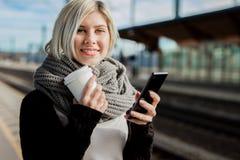 Femme tenant la tasse et le téléphone portable de café à la station de train images stock