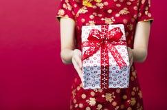 femme tenant le boîte-cadeau sur le fond rouge photos stock