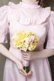 Femme tenant le bouquet de l'oeillet jaune et des roses roses Image stock