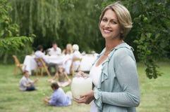 Femme tenant le broc de limonade avec la famille à l'arrière-plan image stock