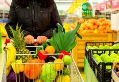 Femme tenant le chariot avec des fruits et légumes au centre commercial image libre de droits