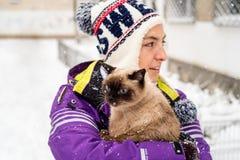 Femme tenant le chat siamois dans la neige Photos stock