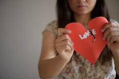 Femme tenant le coeur brisé rouge avec le texte d'amour Image libre de droits