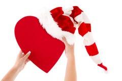 Femme tenant le coeur rouge avec le chapeau de Santa et un coeur pour l'amour Photographie stock libre de droits