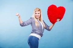 Femme tenant le coeur rouge montrant le pouce vers le bas Image stock