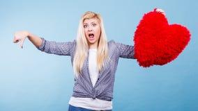 Femme tenant le coeur rouge montrant le pouce vers le bas Images stock