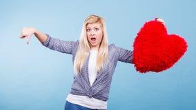 Femme tenant le coeur rouge montrant le pouce vers le bas Photographie stock
