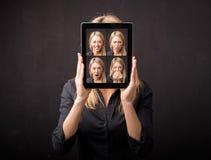 Femme tenant le comprimé avec différents visages devant elle Photographie stock