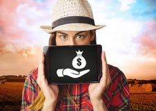 Femme tenant le comprimé avec la main donnant l'icône de sac d'argent Images libres de droits