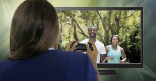 Femme tenant le contrôleur de jeu avec les personnes sportives d'ajustement à la télévision photographie stock
