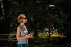 Femme tenant le contrôleur par radio et pilotant un bourdon Photo libre de droits