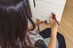 Femme tenant le crayon sur le calendrier pour prendre le rendez-vous photo libre de droits