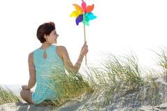 Femme tenant le jouet coloré de moulin à vent Image libre de droits