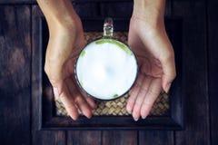 Femme tenant le latte de thé vert de Matcha sur la table en bois Photographie stock libre de droits