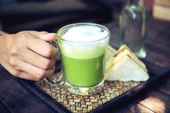 Femme tenant le latte de thé vert de Matcha sur la table en bois Photographie stock