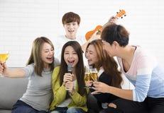 Femme tenant le microphone et chantant au karaoke Photographie stock
