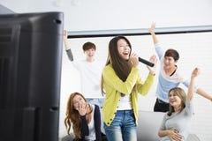 Femme tenant le microphone et chantant au karaoke Photographie stock libre de droits