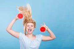Femme tenant le pamplemousse rouge ayant les cheveux ébouriffés par le vent fous Images libres de droits