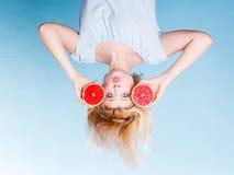 Femme tenant le pamplemousse rouge ayant les cheveux ébouriffés par le vent fous Image stock