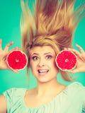 Femme tenant le pamplemousse rouge ayant les cheveux ébouriffés par le vent fous Photos libres de droits