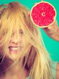 Femme tenant le pamplemousse rouge ayant les cheveux ébouriffés par le vent fous Image libre de droits