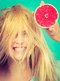 Femme tenant le pamplemousse rouge ayant les cheveux ébouriffés par le vent fous Photo libre de droits
