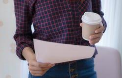 Femme tenant le papier de rapport et la tasse de café Photos stock
