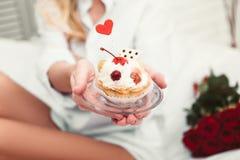 Femme tenant le petit gâteau photos stock