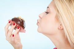 Femme tenant le petit gâteau de chocolat environ sur la morsure Photos stock