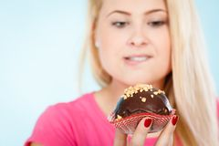 Femme tenant le petit gâteau de chocolat environ sur la morsure Image stock