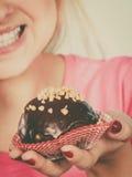 Femme tenant le petit gâteau de chocolat environ sur la morsure Images stock