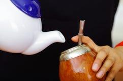 Femme tenant le petit pot blanc versant l'eau chaude dans la tasse traditionnelle avec la paille typique en métal collant, prépar Photo libre de droits
