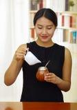 Femme tenant le petit pot blanc versant l'eau chaude dans la tasse traditionnelle avec la paille typique en métal collant, prépar Image libre de droits
