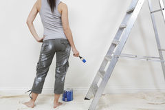 Femme tenant le pinceau contre le mur dans la Chambre Image libre de droits
