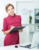 Femme tenant le presse-papiers dans des mains dans le bureau Photos stock
