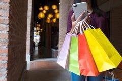 Femme tenant le sac à provisions et à l'aide du smartphone pour faire des emplettes concept en ligne et faisant des emplettes images stock