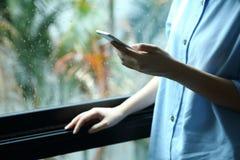 Femme tenant le smartphone avec le contact sur l'écran Photographie stock libre de droits