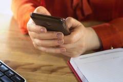 Femme tenant le smartphone dans des ses mains photos stock
