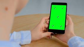 Femme tenant le smartphone noir avec l'écran vert vide - concept clé de chroma banque de vidéos