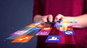Femme tenant le téléphone intelligent avec les icônes colorées d'application Image libre de droits