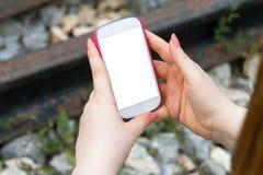 Femme tenant le téléphone intelligent sur le chemin de fer Images stock