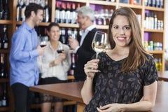 Femme tenant le verre à vin tandis qu'amis se tenant à l'arrière-plan Image stock