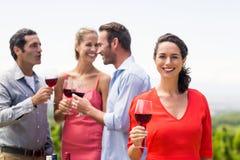 Femme tenant le verre de vin souriant à l'appareil-photo Photographie stock