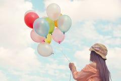 Femme tenant les ballons colorés et volant sur le fond de ciel de nuages Photo libre de droits