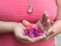 Femme tenant les pétales lilas et roses de bouganvillée dans des ses mains en forme de coeur Image libre de droits