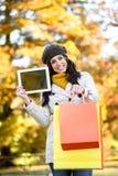 Femme tenant les paniers et le comprimé en automne Photographie stock libre de droits