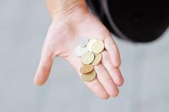 Femme tenant les pièces de monnaie d'or et argentées Image stock