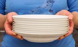 Femme tenant les plats blancs Photographie stock libre de droits
